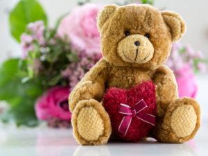 Hab Dich lieb  Teddybr mit Herz und Blumen im Hintergrund