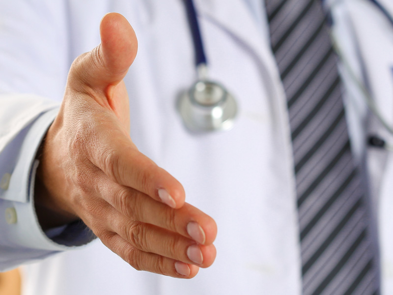Male medicine doctor offering hand to shake in office closeup. Welcoming friend, introduction or thanks gesture. Tests advertisement concept. Physician ready to examine patient. Letterbox view